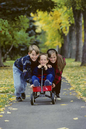 Children playing with wagon Stock Photo