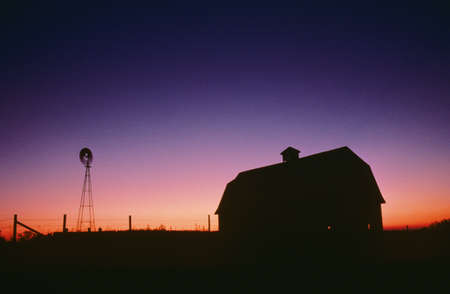 farm structures: Silhouette of barn and windmill Stock Photo