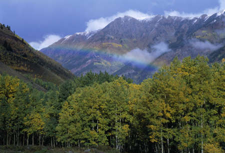 natural selection: Rainbow and clearing storm in a valley between mountain peaks