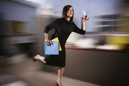 irresponsible: Woman runs with scissors through office Stock Photo