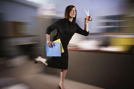 quick: Woman runs with scissors through office Stock Photo