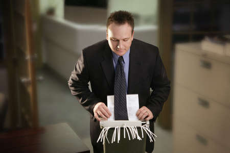 negligent: Office man catches tie in paper shredder Stock Photo