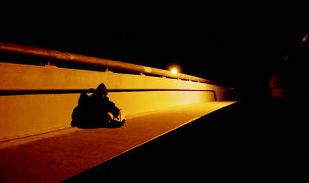 Homeless person on bridge at night