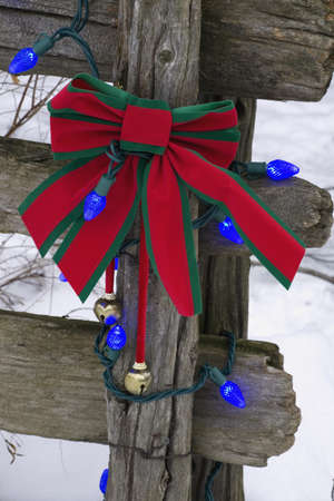 weather beaten: Decorazioni di Natale su una recinzione di legno vecchia nella neve di fuori