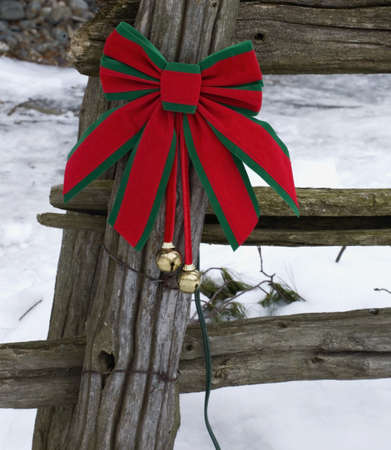 Christmas decorations on an old wooden fence outside in the snow photo