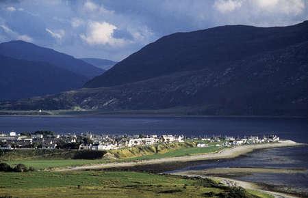 lochs: Ullapool, Scottish Highlands, Scotland, United Kingdom; Quaint village and Loch Broom, beneath mountain range Stock Photo