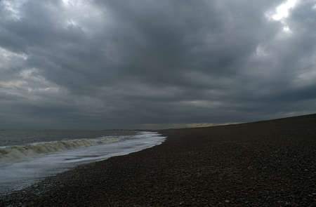 rolling up: East Anglia, England, United Kingdom; Sea water rolling up a gravel beach
