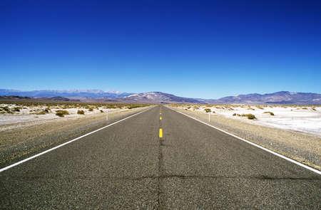 barren: Road leading through barren landscape to mountains