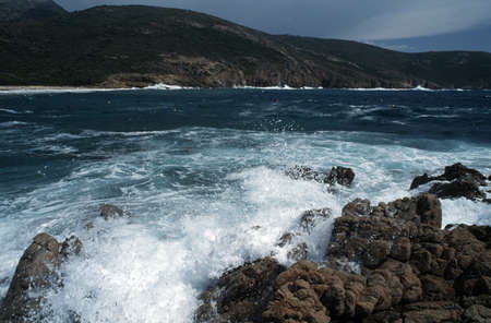 Corsica, France; Waves crashing on a rugged coastline photo