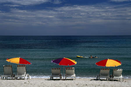 Corsica, France; Lounge chairs and sun umbrellas on a Mediterranean beach
