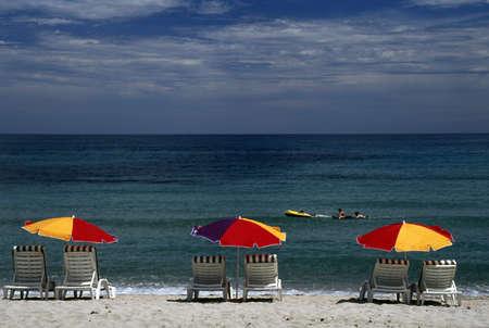 beach chairs: Corsica, France; Lounge chairs and sun umbrellas on a Mediterranean beach