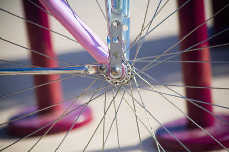 Close up of spokes on a pink bicycle,