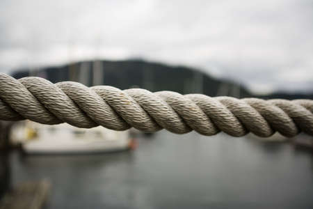 barrier: Close up thick rope, with fishing boats in background