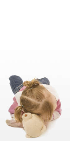 Young girl resting her head on top on a teddy bear photo