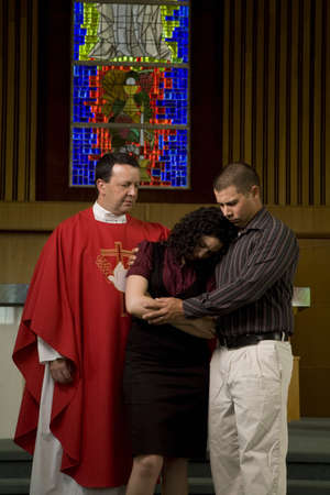 intercessor: Priest ministering to a couple Stock Photo