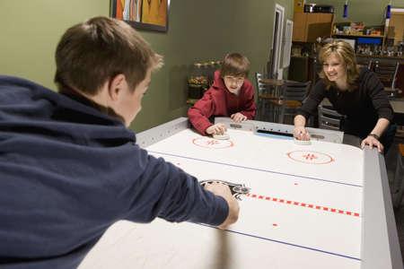 familia jugando: Familia jugar hockey de aire  Foto de archivo