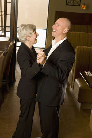 camaraderie: Senior couple dancing and laughing together