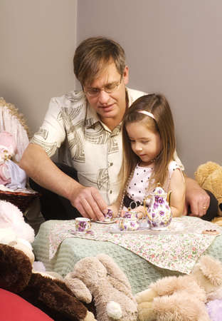 family unit: Father and daughter having tea party Stock Photo