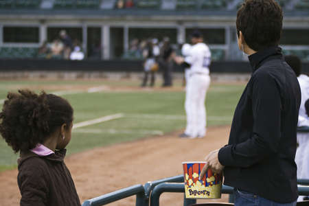 two people with others: Watching a baseball game