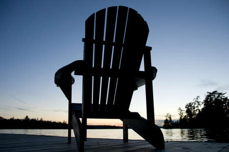 Lake of the Woods, Ontario, Canada; Empty deck chair on a pier next to a lake