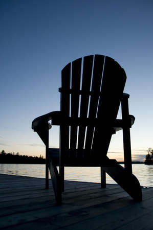 Lake of the Woods, Onta, Canada; Empty deck chair on a pier next to a lake Stock Photo - 7191180