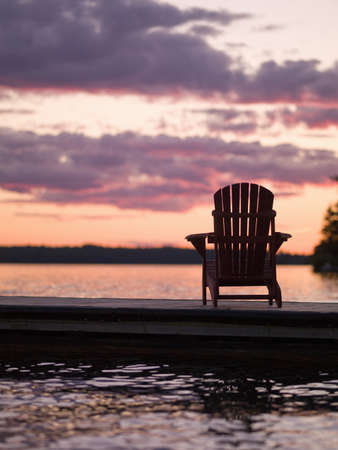Lake of the Woods, Onta, Canada; Empty deck chair on a pier next to a lake Stock Photo - 7213458