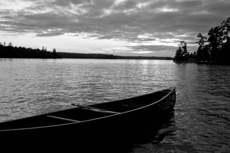 black and white photography: Abandoned canoe floating on water