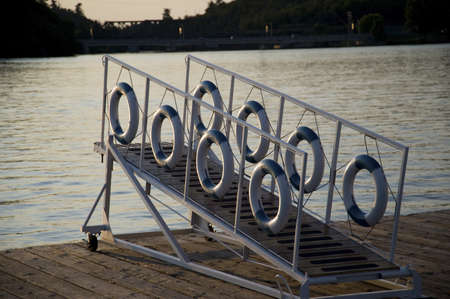 dockside: Kenora, Lake of the Woods, Ontario, Canada; Life preservers hanging on a dockside gangway