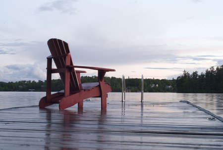 Lake of the Woods, Ontario, Canada; Empty deck chair on a pier next to a lake Stock Photo - 7190330