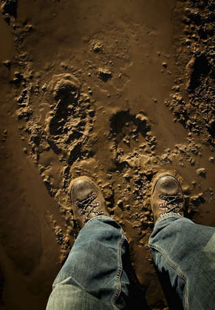 hiking boots: Low section of person standing in mud
