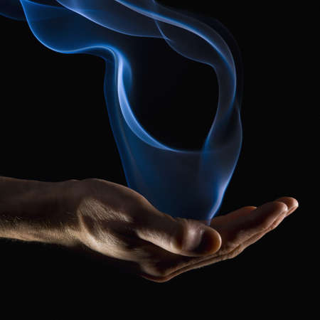wafting: Smoke wisps from a hand Stock Photo