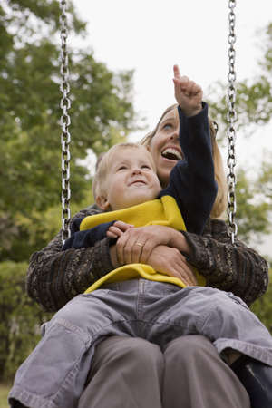 Mother and son on a swing photo