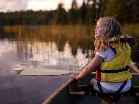 long lake: Lake of the Woods, Ontario, Canada; girl in a canoe   Stock Photo