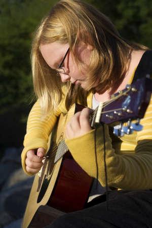 Teen playing guitar photo