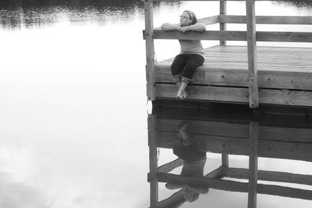 full length mirror: Girl sitting on a dock Stock Photo