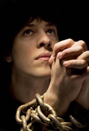 arrepentimiento: Hombre en las cadenas, rezando  Foto de archivo