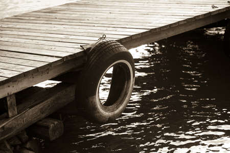lake fronts: Tire hanging from dock, Lake of the Woods, Ontario, Canada Stock Photo
