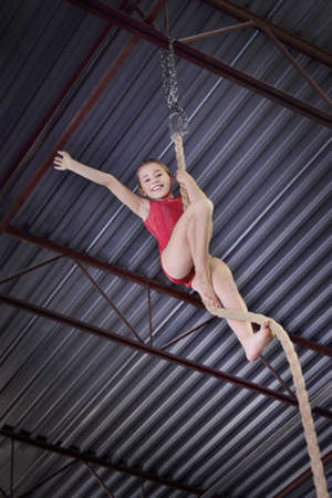leah: Child climbing a rope in gymnastics
