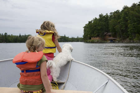 lakeshores: Children in boat with dog, Lake of the Woods, Ontario, Canada Stock Photo