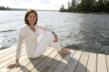 Woman relaxing on dock, Lake of the Woods, Ontario, Canada Stock Photo
