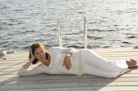 lakeshores: Woman relaxing on dock, Lake of the Woods, Ontario, Canada Stock Photo