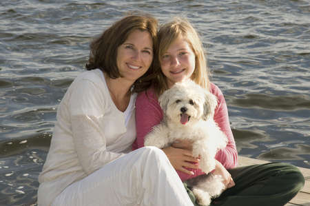 Mother and daughter on dock with dog, Lake of the Woods, Ontario, Canada photo