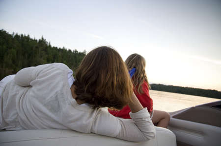 preadolescent: Enjoying sunset from boat, Lake of the Woods, Ontario, Canada