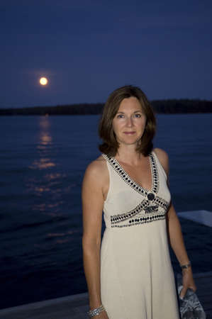 lakeshores: Woman on dock at night, Lake of the Woods, Ontario, Canada Stock Photo