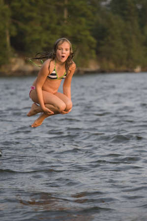 lakeshores: Young girl jumping into lake, Lake of the Woods, Ontario, Canada