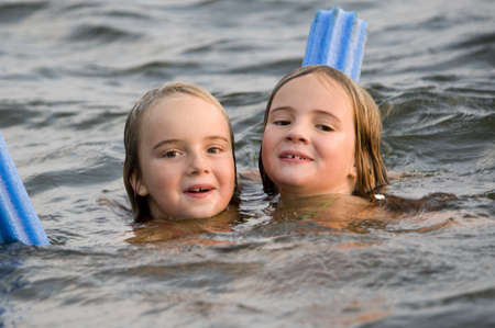 Young girls swimming in lake, Lake of the Woods, Ontario, Canada photo