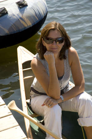 Woman in canoe by dock, Lake of the Woods, Ontario, Canada photo