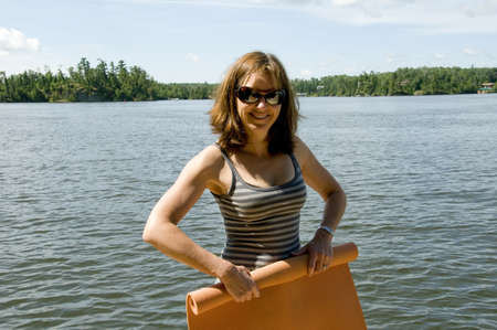 lakeshores: Woman rolling up yoga mat, Lake of the Woods, Ontario, Canada