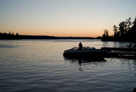 Boat by dock at sunset, Lake of the Woods, Ontario, Canada photo