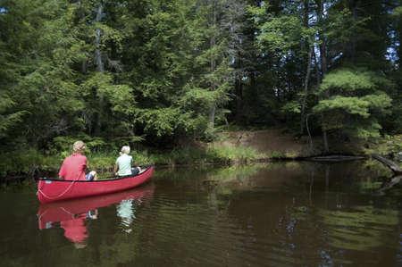 canoeing: Muskokas, Ontario, Canada; couple canoeing down a river